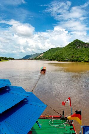 river boat towing raft down river in asia