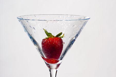 wet strawberry in martini glass