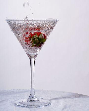 splashing wet strawberry in martini glass