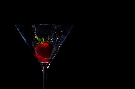 wet strawberry in martini glass on black Stock Photo