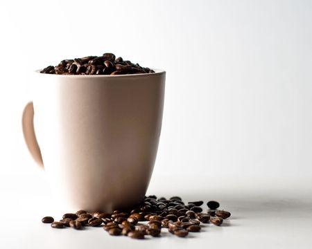 grains de caf� en tasse isol� sur blanc
