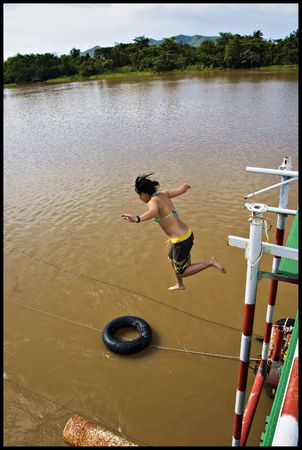 ethnic girl jumping off river boat in thailand Stock Photo