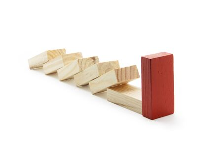 Be different concept. One red wooden domino pushed forward in a series between the wooden block on white background