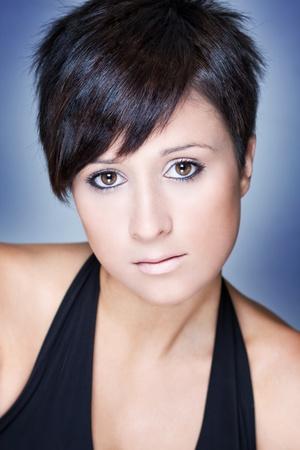 hair short: Ritratto di moda di una bella donna con i capelli corti. Sfondo blu.