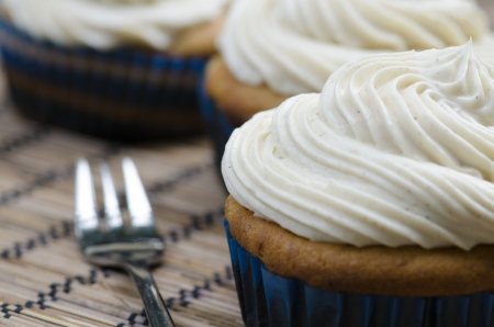 Three decorative iced cupcakes topped with white twirled icing on a placemat with a fork, low view angle with shallow depth of field Stock Photo