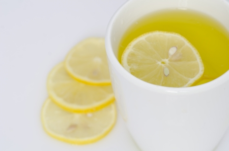 Mug of hot lemon tea with three thin slices of lemon displayed on a white surface