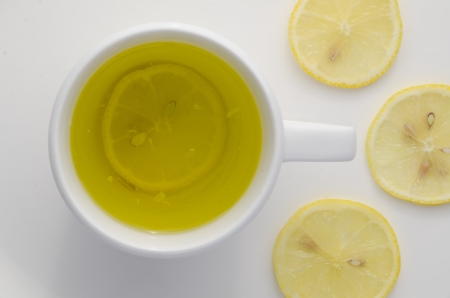 Overhead view of a mug of hot refreshing lemon tea with sliced lemon on a white background