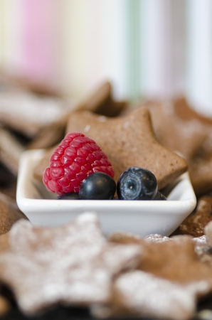 Bowl with fresh raspberry  blueberries and a tasty freshly baked star cookie in a traditional Christmas seasonal