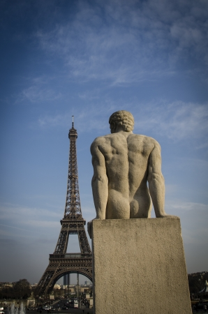 Statue of a man at the Trocadero sitting with his back to the viewer looking at the Eiffel Tower in Paris Stock Photo