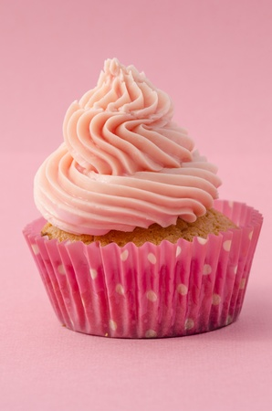 Decorative birthday cupcake with twirled icing and a pink background