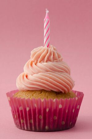 Decorative birthday cupcake with twirled icing and a single candle on a pink background