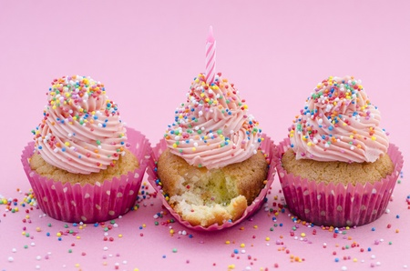 Party cupcakes for a birthday celebration decorated with twirled pink icing  colourful sprinkles and a single candle in the central one which has a small section broken off in front