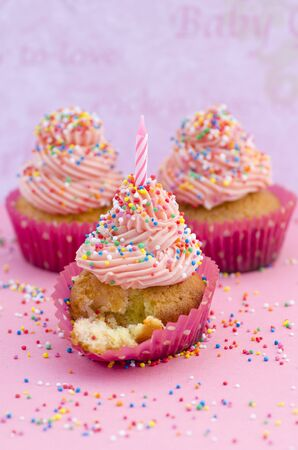 Delicious birthday cupcake with twirled pink icing decorated with colourful sprinkles and a candle on a pink surface