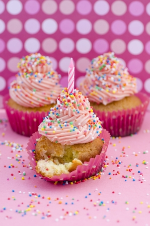 Partytime with cupcakes - a group of three delicious decorative cupcakes with twirled pink icing sprinkled with colourful sprinkles and a single birthday candle on a pink polka dot background