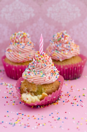 Freshly baked colourful birthday cupcake decorated with twirled pink icing  multicoloured sprinkles and a single unlit candle on a pink background with copyspace