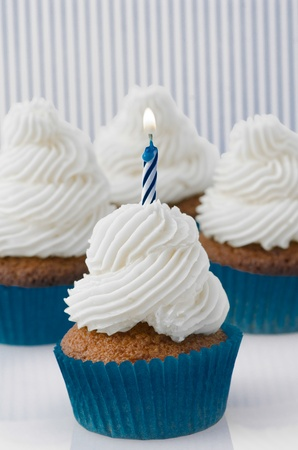Beautiful freshly baked birthday cupcake with twirled icing and a single burning spiral twist candle