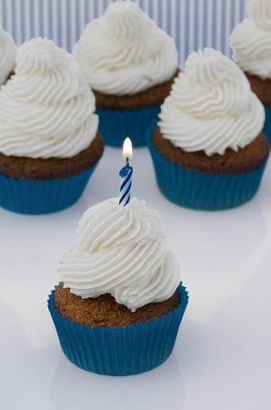Freshly baked red velvet cupcake with cream cheese frosting and a single burning spiral birthday candle standing in front of several more cupcakes