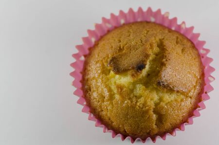 overhead tasty fresh golden  cupcake in a pink fluted casing for a special occasion on a pink studio background