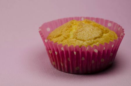 Tasty fresh golden  cupcake in a pink fluted casing for a special occasion on a pink studio background with copyspace Stock Photo