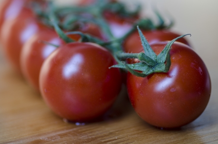 Closeup with shallow dof of a bunch of ripe red grape tomatoes on the vine