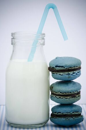 Fresh creamy milk in a glass bottle with a straw standing alongside three stacked blue macarons or macaroons Stock Photo - 20932329