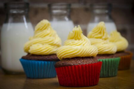 Closeup of colourful red velvet cupcakes topped with a delicious swirl of cream cheese frosting ready for a party celebration