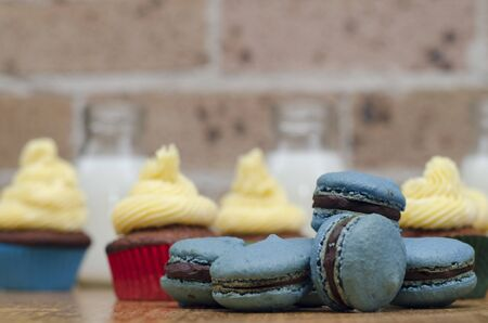 Red velvet cupcakes with colourful blue macarons or macaroons made from egg white  sugar and almond paste in the foreground  home baked for a party celebration Stock Photo