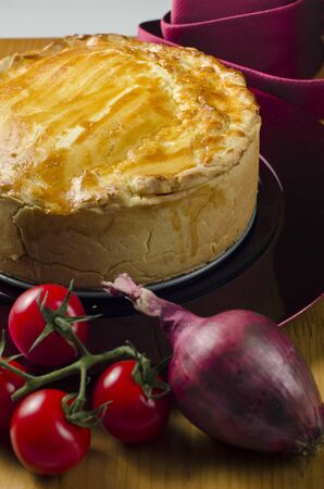 Delicious homebaked meat pie with a crisp golden crust with cherry tomatoes and a red onion in the foreground