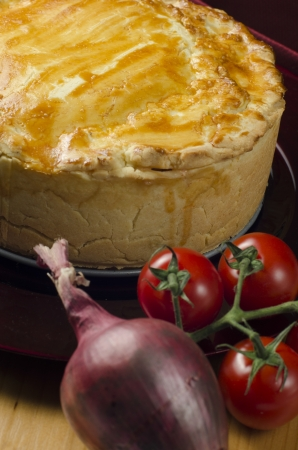 High angle closeup view of a delicious freshly baked golden meat and vegetable pie standing in the kitchen with cherry tomatoes and a red onion Stock Photo