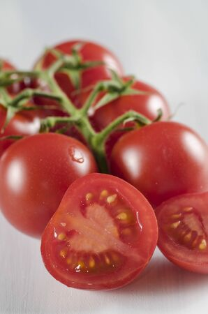 Halved ripe red juicy cherry tomato together with whole tomatoes on the vine displayed on a kitchen counter