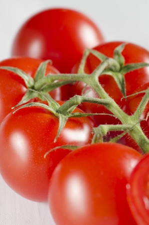 Closeup of a bunch of succulent ripe red cherry tomatoes on the vine for use as a cooking ingredient and in salads