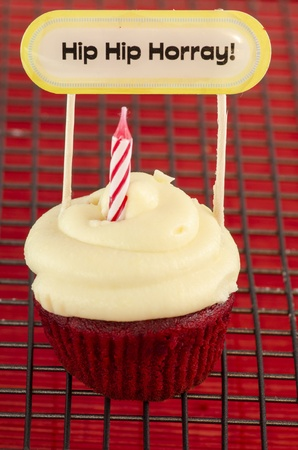 Birthday cupcake with a candle and a note with the words: Hip  hip  hurray! Stock Photo