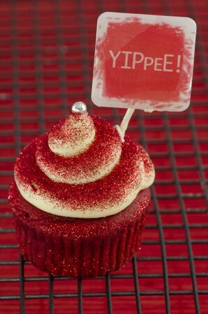 Red cupcake with a twirl on a grate with a note and the word: Yippee! Stock Photo