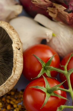 Closeup of fresh cherry tomatoes and a mushroom ready for use as ingredients in cooking a healthy vegetarian meal
