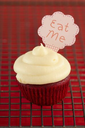 Cupcake with cream and a note with the words  Eat me photo
