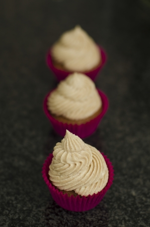 Red velvet cupcakes with decorative swirl of cream cheese frosting arranged in a receding row with shallow dof Stock Photo - 21072105