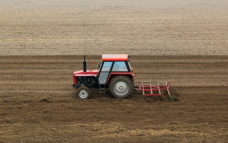 red tractor in a plowed field - agricultural scene