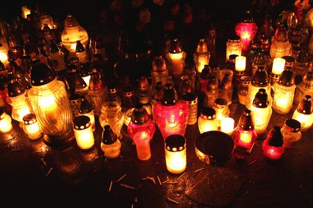 heaven and hell: Red and yellow candles flames on grave during All Saint Stock Photo