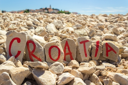 croatia: Croatia text painted on stones beach with dalmatian town in the background Stock Photo