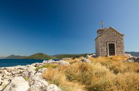 croatian: Small old stone church on island in Klek, Dalmatia, Croatia, Europe
