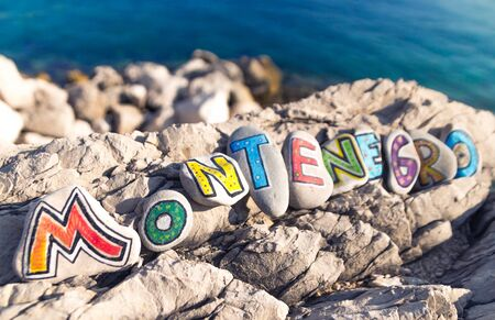 Montenegro name made of colorful painted stones on sea background Stock Photo