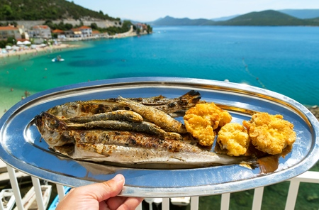 view on sea: A plate of delicious grilled fish and a beautiful view of the blue sea Stock Photo