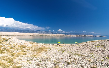 Beautiful Pag croatian beach, mountains in the background and blue water