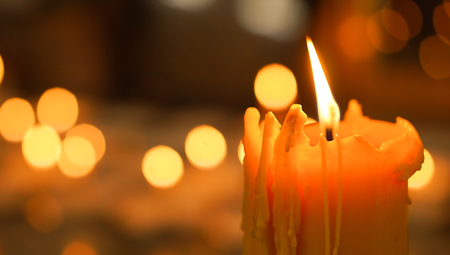 One candle flame with bokeh in thai temple.