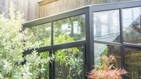 Vintage glass house and green plants with flare light Standard-Bild