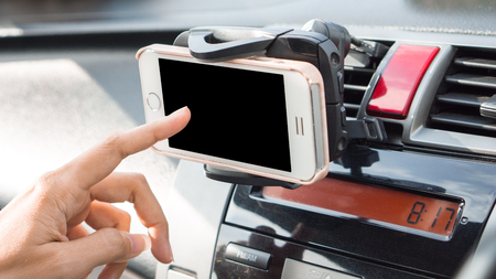 mobile phone and transportation concept - Car panel mobile phone holder device with woman using on car driving Standard-Bild