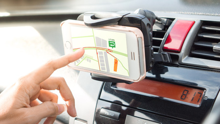 GPS mobile phone and transportation concept - Close up driver hand using navigation or gps on mobile smartphone. with flare lighting effect
