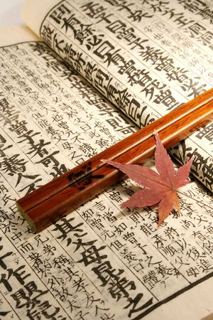 Old Japanese book from meiji period with chopsticks and japanese maple leaf