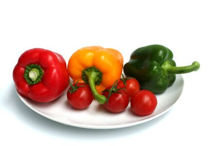 some red, green and yellow peppers on a plate with red tomatoes Stock Photo