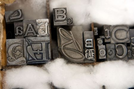 moveable: Metal type blocks, used for letterpress printing. Mixed type in a wooden tray with cotton wool packing.